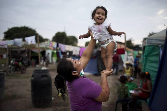 Patricia Sambrano juega con su nieta en una carpa improvisada por familias que lo perdieron todo en Canoa, Manabí. AP/Rodrigo Abad) AP